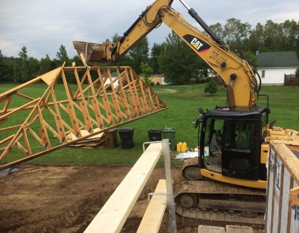 Machine en train de soulever une structure de toiture
