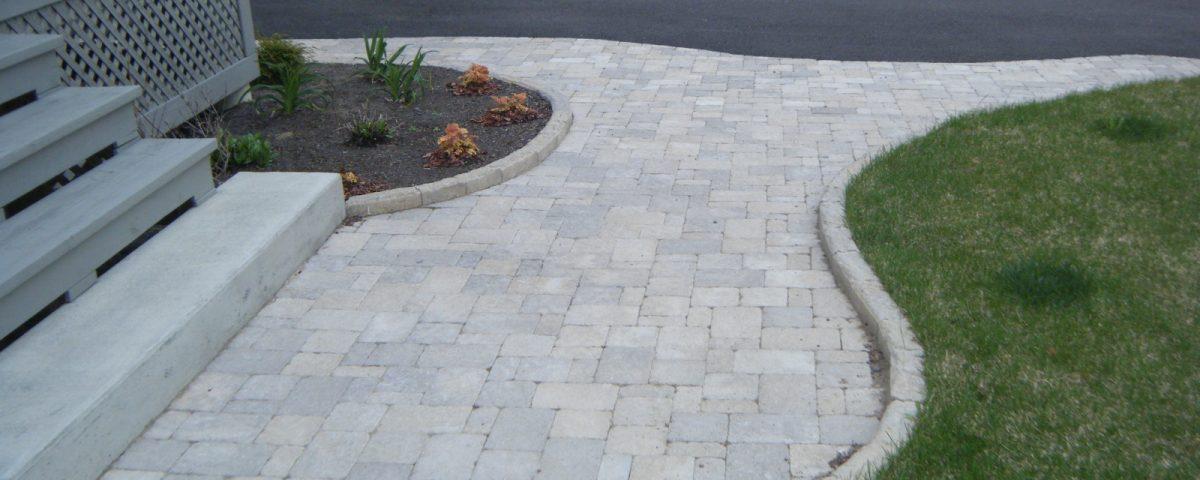Pavage - Entrée pavée d'une maison avec gazon et stationnement asphalté