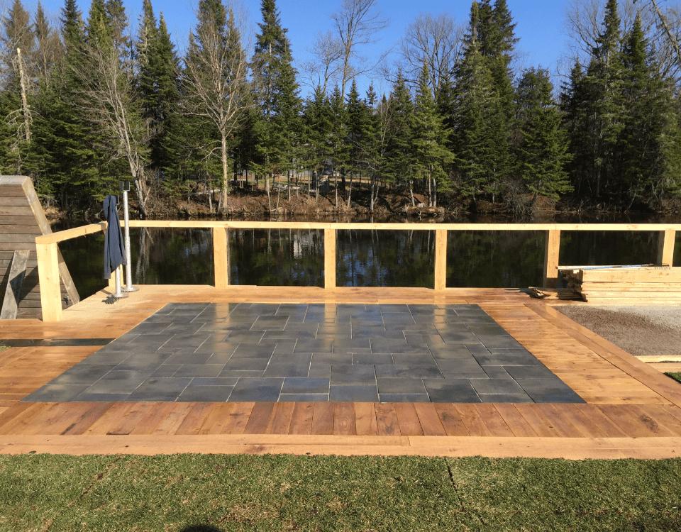 Aménagement paysager d'une terrasse pavé et gazon avec vue sur un lac