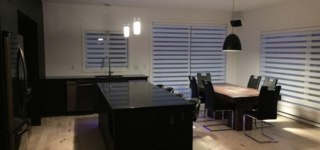 Cuisine à aire ouverte avec salle à manger. Planchers de bois. Bar, comptoirs, électroménagers et chaises de couleur noire.