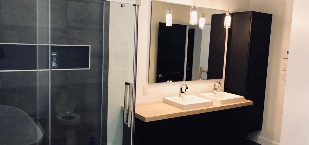 Salle de bain très récente de couleur noire et blanc avec deux lavabos une douche et une baignoire