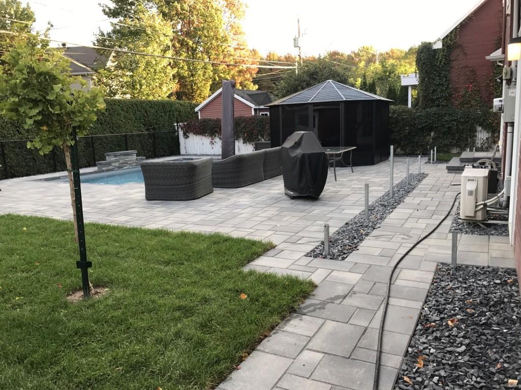Terrasse aménagé avec pavés et gazon. Il y a une piscine avec un coin détente pour manger