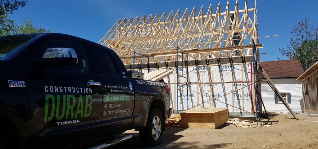 Pick-up de Construction Durab en premier plan avec la construction d'une maison en arrière-plan